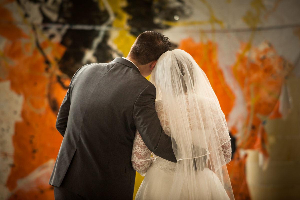 bruidspaar op de rug in omhelzing bij kunstwerk