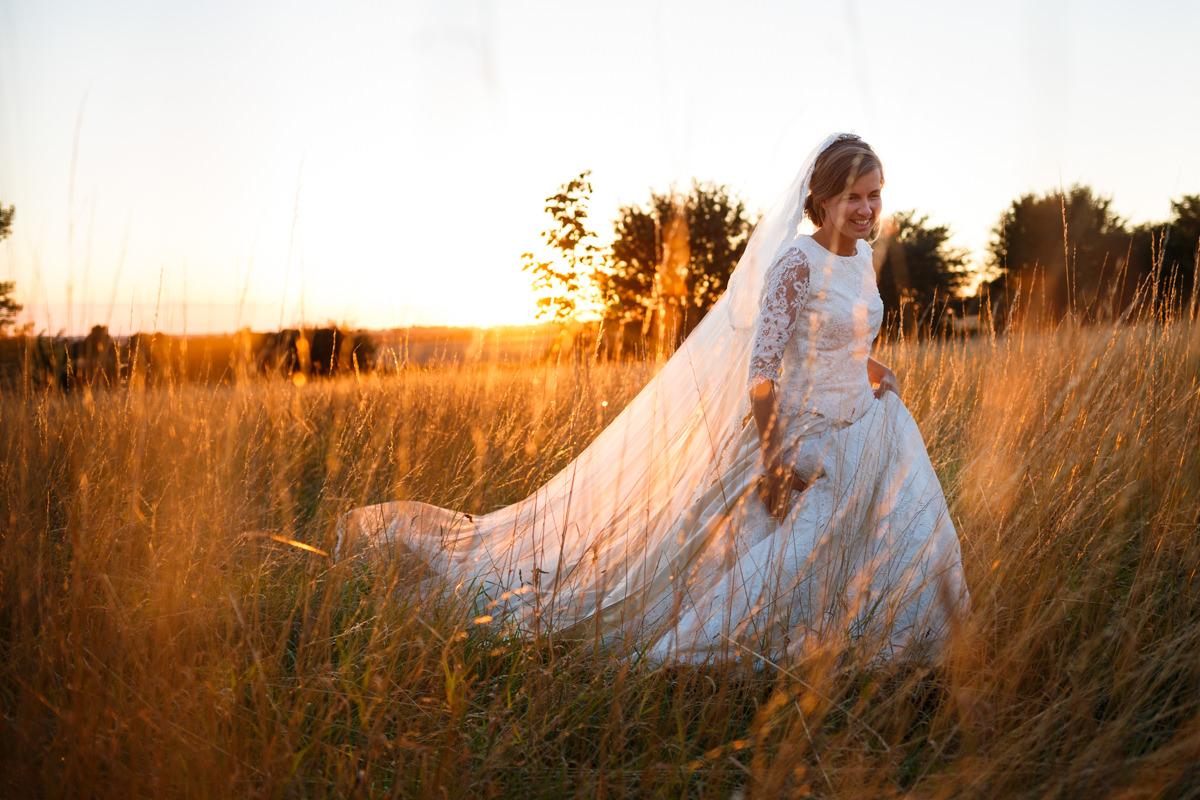 bruid en trouwjurk door hoge grassen tijdens zonsondergang