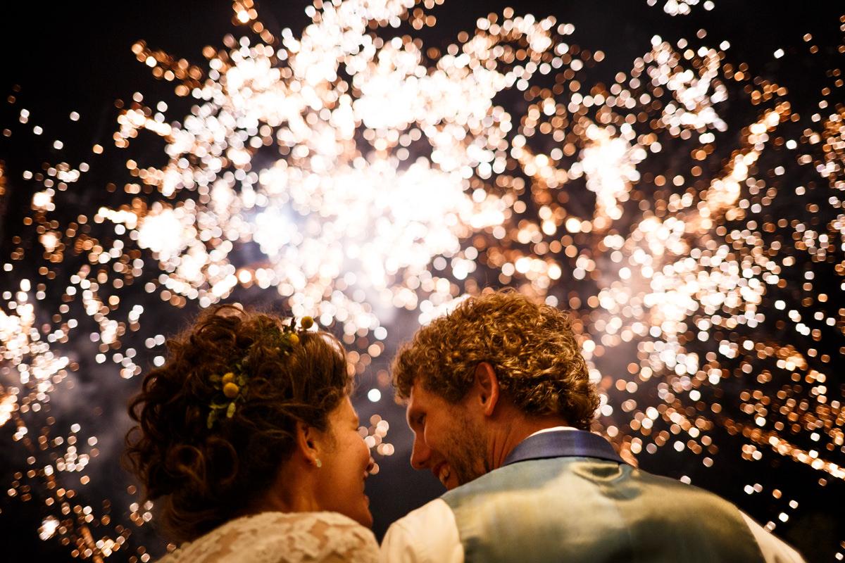 bruidspaar 'savonds tegen achtergrond van vuurwerk