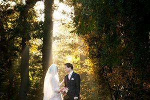 verhalende trouwfotografie Rijssen, bruidspaar staand in gouden ochtendlicht bundel die valt tussen bomen over bedauwd gras