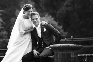 verhaalvertellende trouwfotografie, Warmelo, bruidspaar bij muur, bruidegom zittende zwart/wit