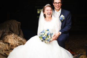 verhaalvertellende trouwfotografie, Rijssen, zittend lachend bruidspaar bij schaapskooi
