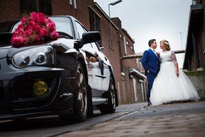 verhaalvertellende trouwfotografie, Almelo, bruidspaar op oude industrie locatie met Subaru trouwauto en boeket